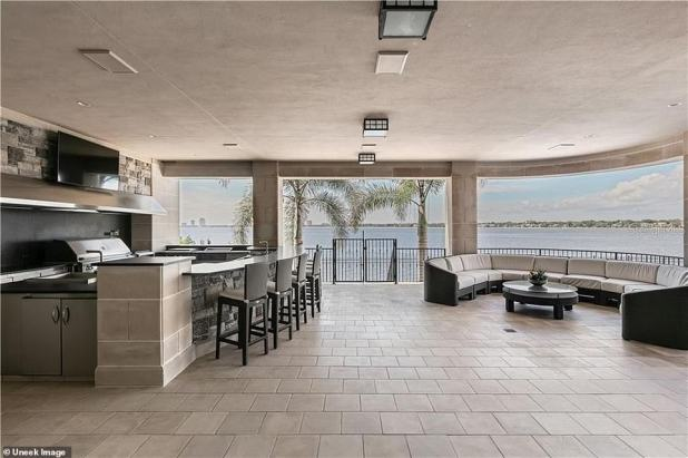 Outdoor Glam: A second covered kitchen is located outside the house and has a flat screen TV, bar, grill and lounge area