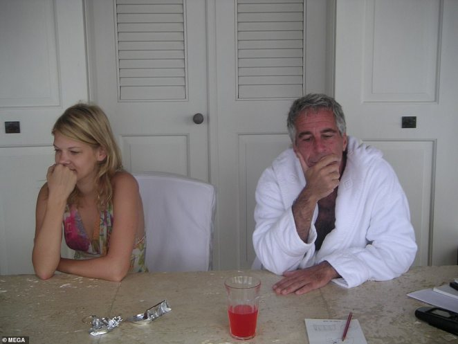 Epstein appears to be in deep thought while conducting business in a plush bathrobe while Marcinkova sits next to him