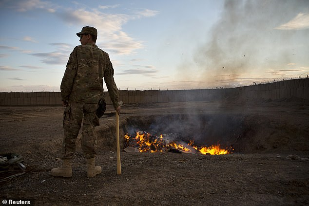 A U.S. Army soldier watches bottled water that had gone bad burn in a burn-pit at Forward Operating Base Azzizulah in Maiwand District, Kandahar Province, Afghanistan, in 2013
