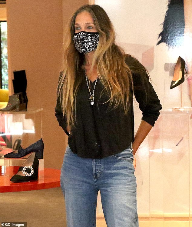 Casual: Parker kept it casual in jeans and a long sleeve shirt as she spent the day in Midtown helping customers at her store