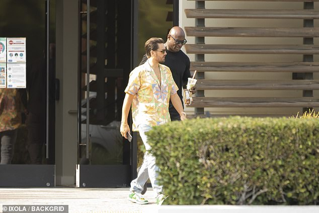 Scott's look: Disick was spotted wearing a partially unbuttoned multi-colored button down shirt and light blue jeans