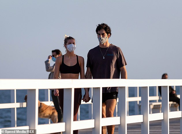 Locals wearing face masks walk along the South Melbourne Beach on Monday. Lockdown restrictions in regional Victoria will be lifted from tomorrow