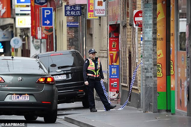A police officer is seen on Little Bourke St where Ms Angok's dead body was found on April 24, 2019