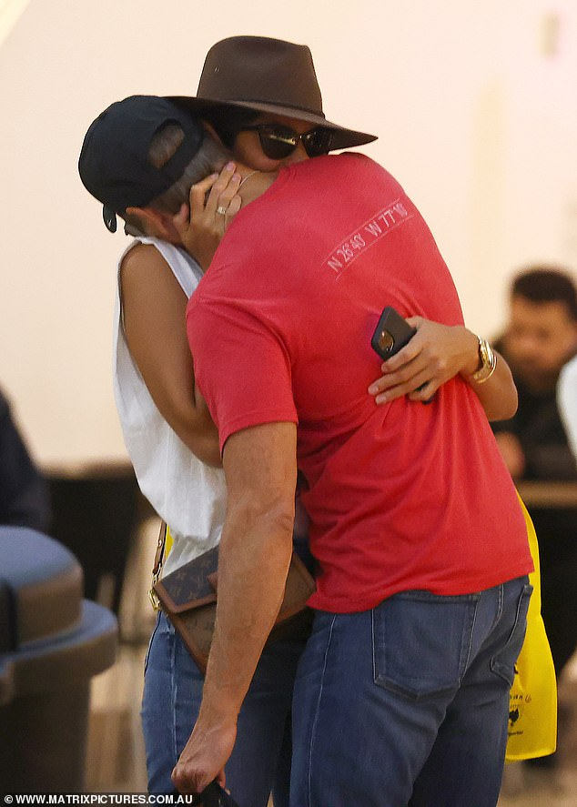 Together again: After hours of shopping, the lovebirds packed on the PDA as they shared a smooch after ordering a meal