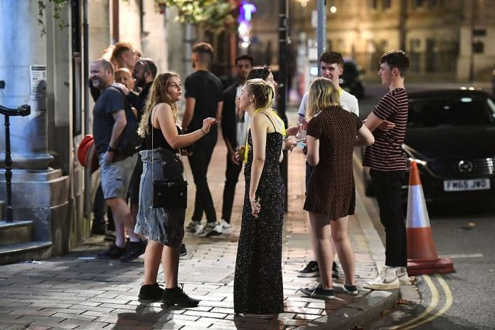 A group of revellers gather outside a bar in Guidhall Walk in Portsmouth without masks amid the coronavirus pandemic