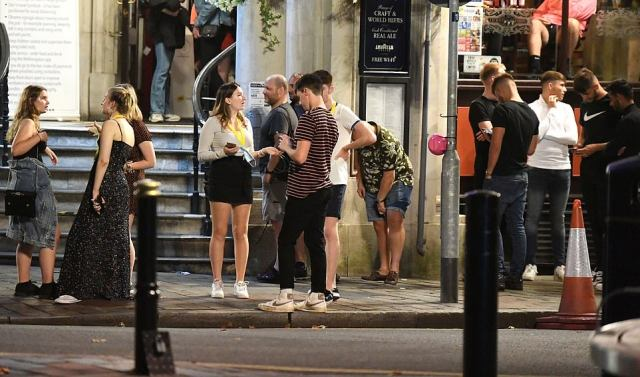 Part-goers without face coverings gather outside in Portsmouth, Hampshire, on Tuesday as they enjoy a night out