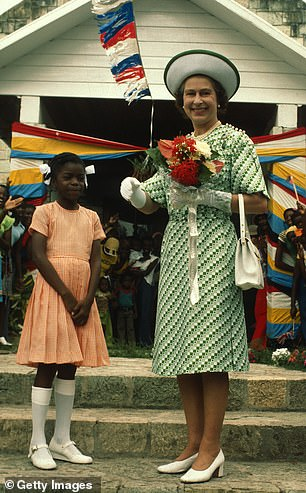 Queen Elizabeth ll smiles with a young girl in Barbados on November 1, 1977
