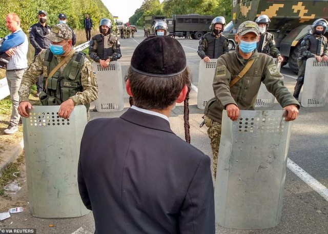 A Jewish pilgrim, who plans to enter Ukraine for a pilgrimage from the territory of Belarus, stands in front of Ukrainian service members near Novi Yarylovychi crossing point in Chernihiv Region, Ukraine September 15
