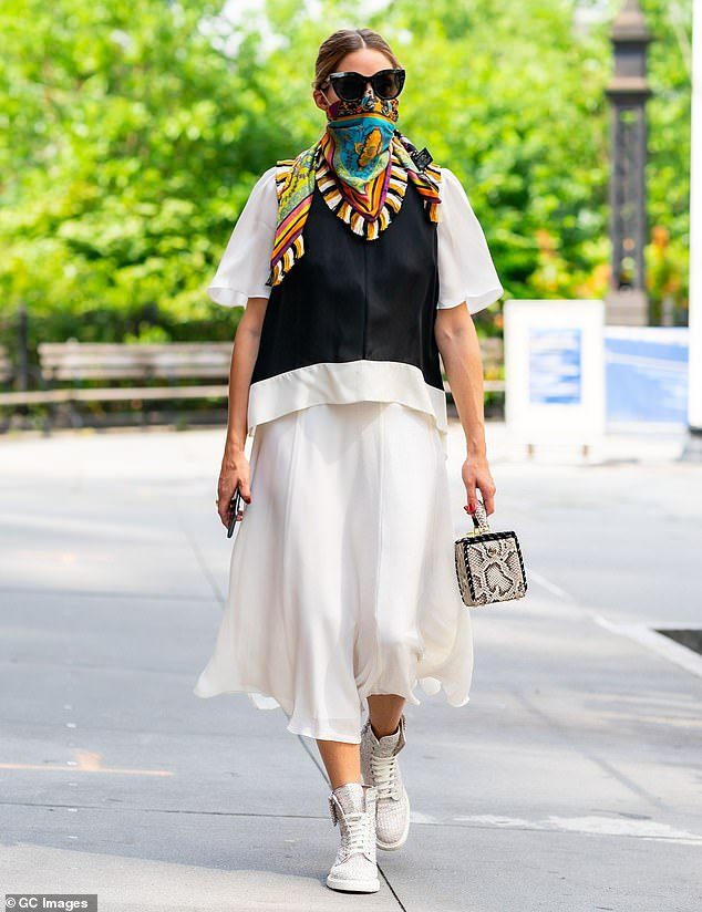 Safety first: Olivia Palermo has shown how a silk scarf - once tied around the head a-la-the Queen - can be re-purposed as a face covering for the fashion-conscious in the age of Covid-19