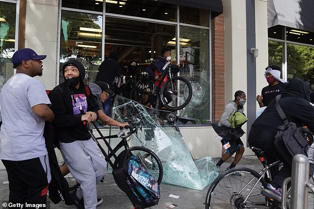 People run off with merchandise from a store during widespread protests and unrest in response to the death of George Floyd in Santa Monica, California, on May 31