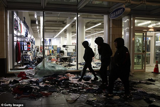 People walk past a store that was looted during a riot following a rally expressing outrage over the death of George Floyd on May 30 in Seattle. Insurance companies will pay out up to $2billion in claims for property damage caused during the nationwide rioting