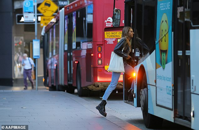 Demand for used cars has soared during the coronavirus pandemic with Australians (woman on a Sydney bus pictured) driving the price up by 25 per cent compared to August 2019