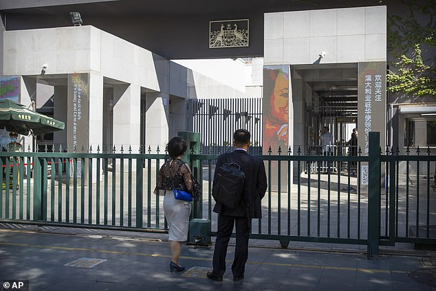 People standing at the gates of the Australian Embassy in Beijing, China, following Australian TV anchor Cheng Lei being arrested on August 14