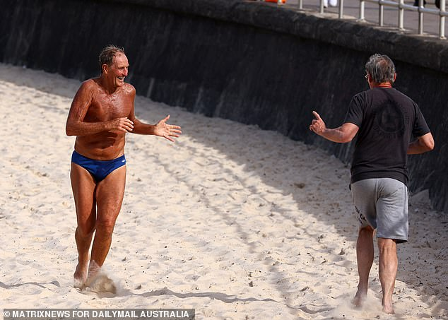 Two men greet each other with a socially distanced wave as they go for a run on Bondi Beach