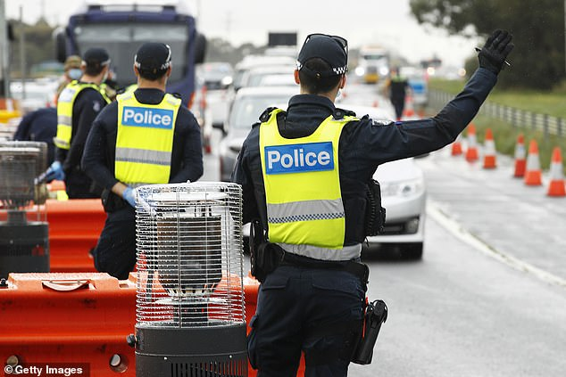Police and ADF check work permits and identification at a road block in Little River on September 17 in Geelong