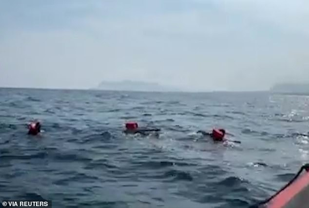 The Sicilian coast can be seen in the background as migrants wearing orange life jackets attempt to swim to shore