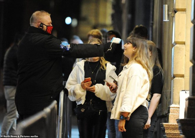 A reveller has her temperature checked by a bouncer before entering a venue in Newcastle city centre this evening
