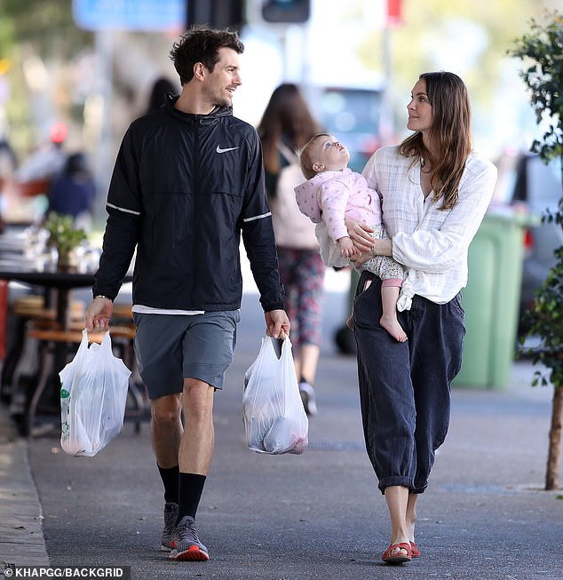 Casual and comfy:Laura wore a billowing white blouse and a pair of charcoal baggy trousers as the couple went shopping in Bondi Beach