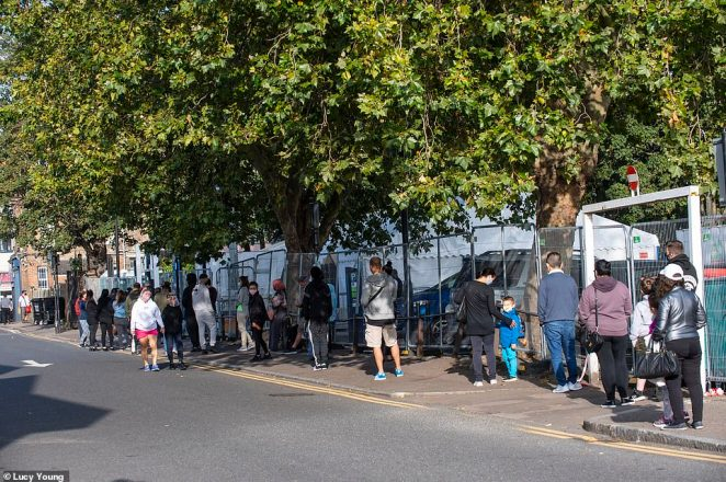 Members of the public are pictured queueing outside a coronavirus testing centre in Edmonton, North London, as people across the country say they are struggling to get hold of tests