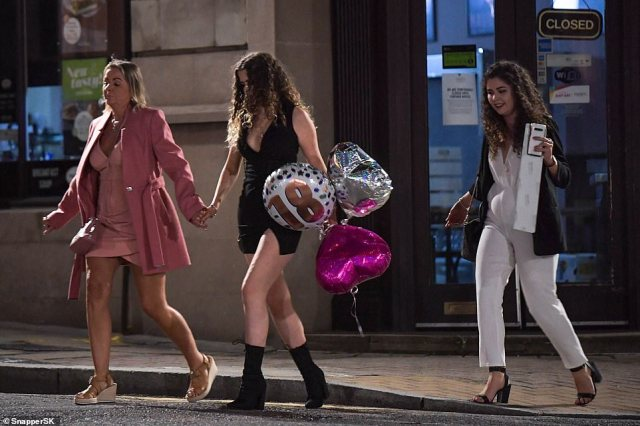 Pictured: A woman celebrating her 18th birthday carries balloons as she heads out in Birmingham on Thursday night