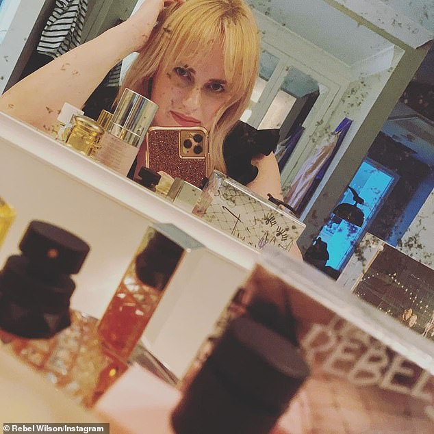 The Isn't It Romantic actress wrote in her caption: 'Finishing touch - perfume... but which one?'