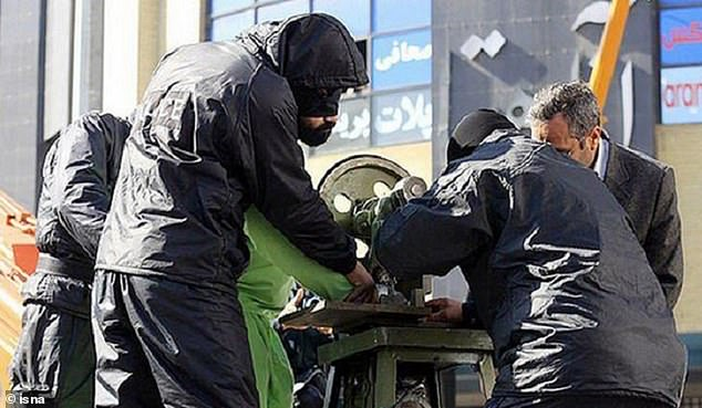 Iran has sentenced three teenagers to have four fingers amputated from their right hands as a punishment for stealing in the city of Urmia (file image, a man has his hand placed into a machine that Iran uses to amputate fingers)