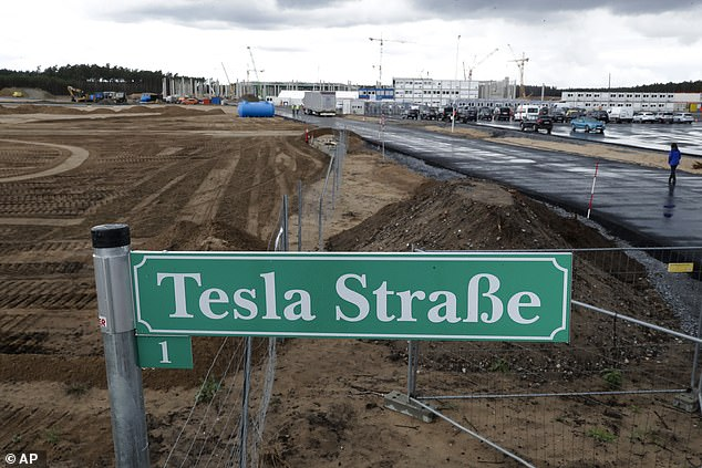 A street sign reading 'Tesla Street 1' stands in front of the construction site of the electric car Tesla Gigafactory in Gruenheide