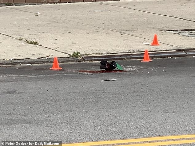 A baseball cap is seen resting in a pool of blood following an execution-style shooting of 33-year-old Felix Medina in The Bronx on Thursday