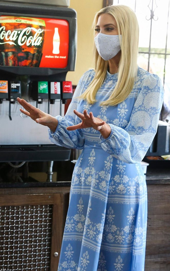 Outfit of the day: The 38-year-old donned a light blue and white patterned dress with billowy sleeves and a matching Lele Sadoughi pinstriped face mask adorned with pearls