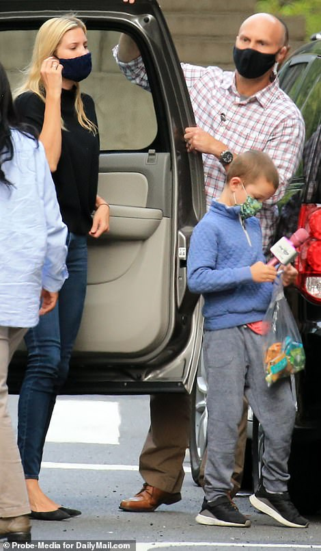 Keeping him occupied: The little boy carried was appeared to be a small bag of snacks and a bright pink toy microphone