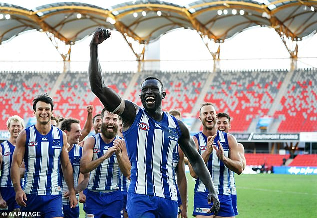 Daw raises a fist while leading the Kangaroos from the field at Metricon Stadium after his fairytale return to the AFL on the Gold Coast on August 1