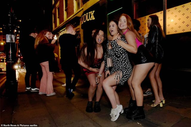 Three revellers pose for a photograph in Newcastle city centre as bars closed at 10pm last night under new curfew rules