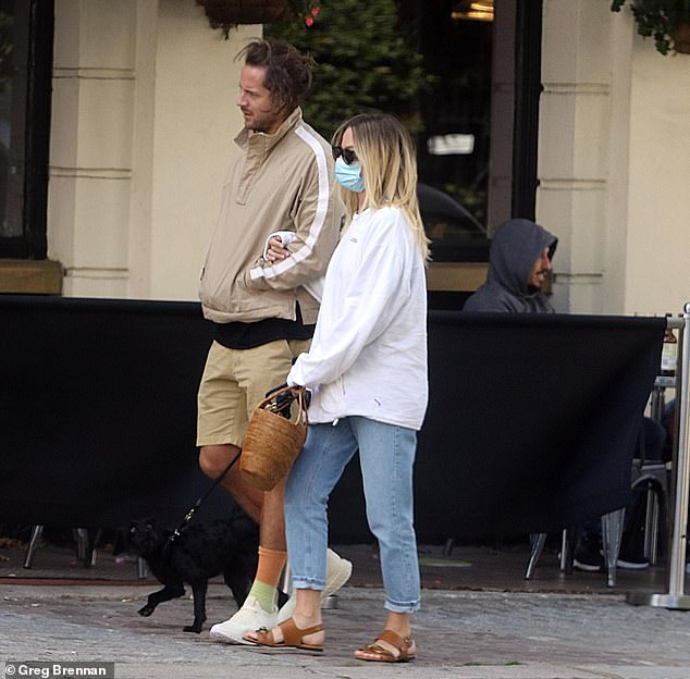 Relaxed: Wearing her golden tresses in tousled waves, Margot looked relaxed and happy as she strolled with producer Tom, who donned a taupe windbreaker with khaki shorts