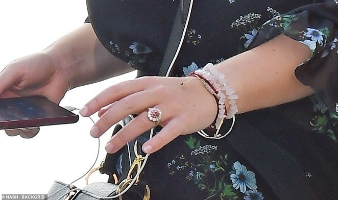 With her two 1.5 carat pear-shaped diamond wedding ring gleaming in the sunshine, the Princess looked a little distracted on her phone as she walked through town with her earphones on