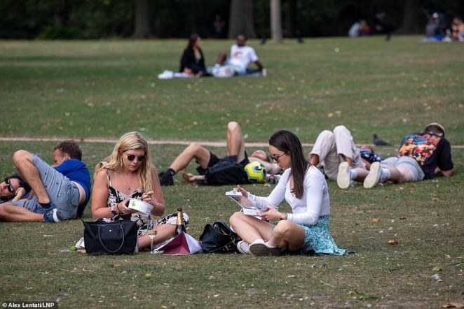 The Met Office had forecast a weekend of 'largely dry, bright and fine' weather, which could see temperatures rise as high as 24C (75F). Pictured, picknickers enjoy the warn sunshine on the first weekend the 'rule of six' is in force