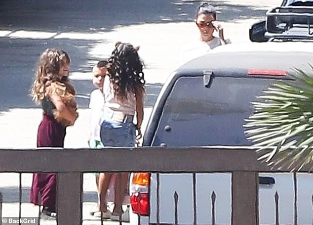 Gang's all here: She was accompanied by daughter Penelope Scotland, eight, son Reign Aston, five, and niece North West, seven