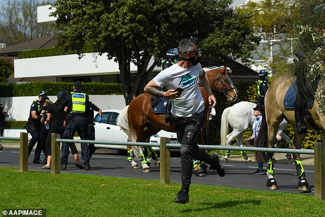 A man ran from police as mounted officers chased protesters down a street during Saturday's protest