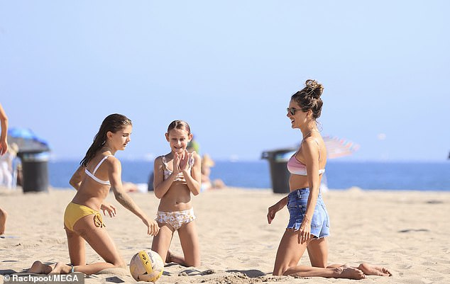 Playing in the sand:The ex-wife of Jamie Mazur was also seen with her daughter Anja Louise, 12, along with another friend as they knelt in the sand, playing with the volleyball