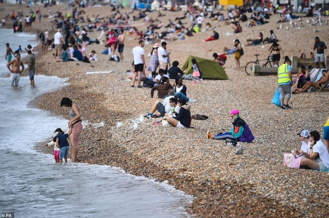 People enjoy the weather at Brighton Beach today. 100,000 weekend visitors rushed to Brighton with highs hotter than the 23C Algarve at nudging 27C - 8C above average