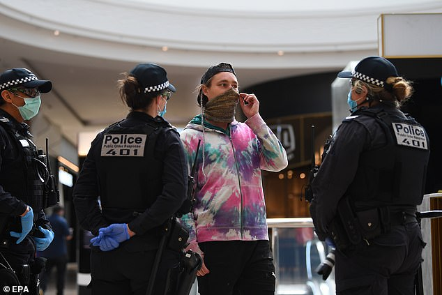 Victoria recorded just 14 new infections on Sunday, the lowest number in three months.  Pictured: Police talk to a protester on Sunday