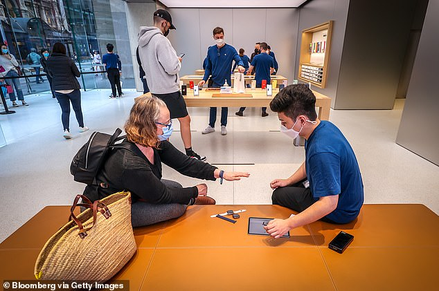 An employee wearing a face mask serves a customer at the Apple store in Sydney on Friday