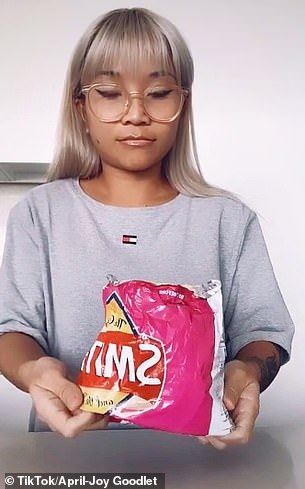 She keeps scrunching the packet until the chips are close to the top