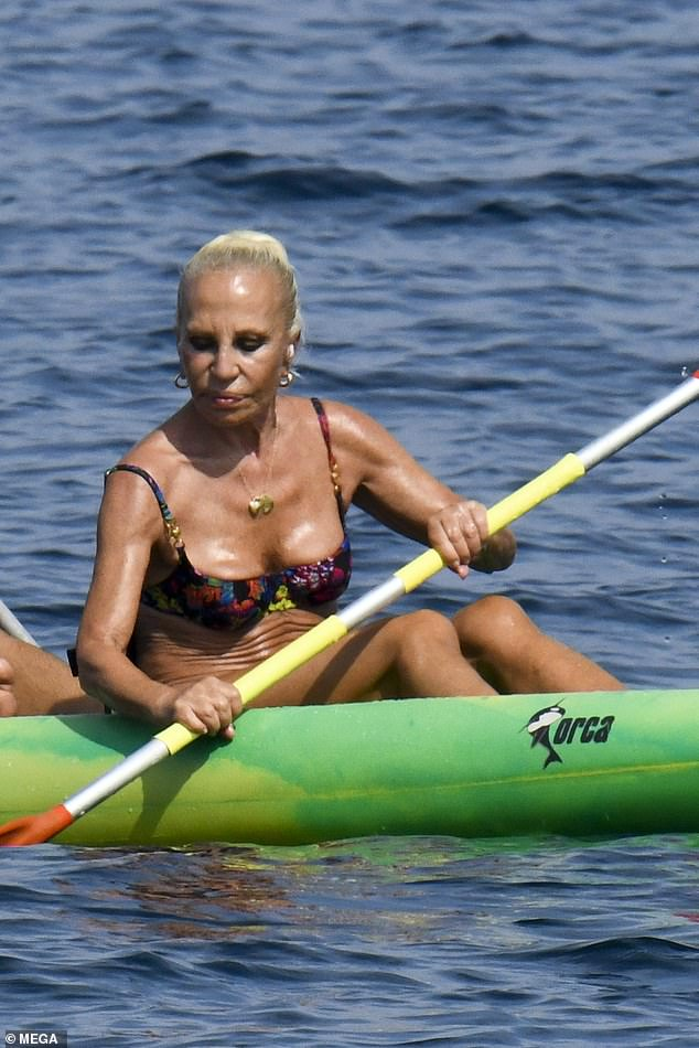 Chic:One of Donatella's ensembles featured a colourful floral print on a blue bikini, and the revealing top ensured she showed off a glimpse of her cleavage