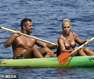 Sporty: Donatella showed off her slender physique as she enjoyed a spot of kayaking with a male companion before taking a dip in the crystal blue ocean