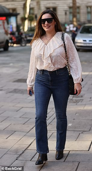 Lovely: The model teamed the classy top with boot-cut jeans and boots