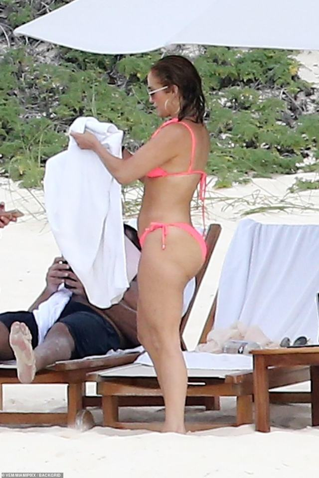 Easy: After cooling off in the water, she slicked back her shoulder-length hair and wore a pair of over-sized sunglasses
