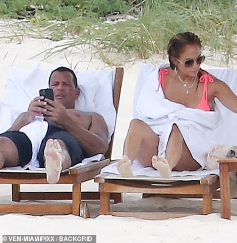 Making money moves: He typed away on his phone while JLo relaxed