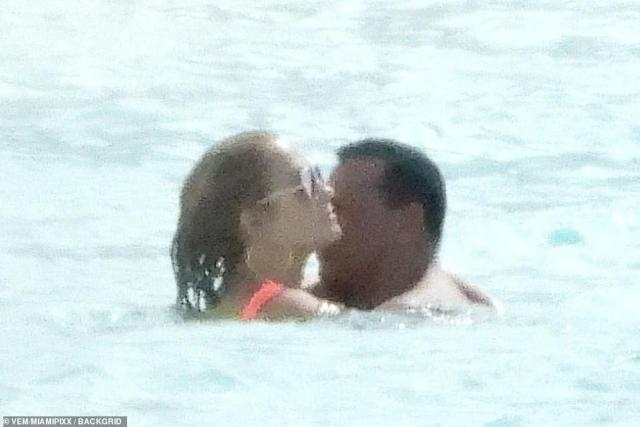 Loved up: JLo wrapped her arms around her beau while the couple played in the water before taking a break on shore