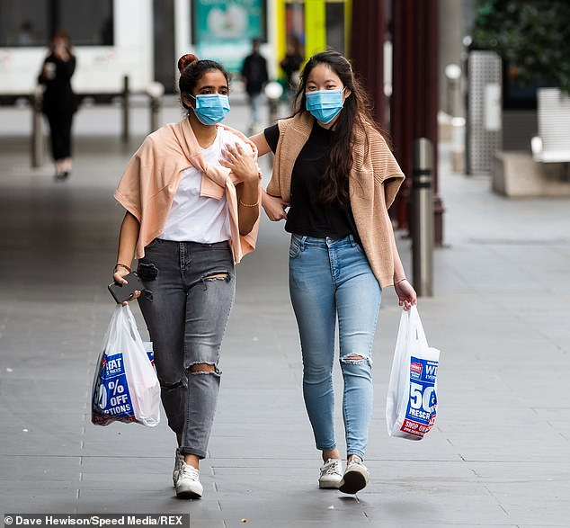 Two woman wearing facemasks carry their shopping during lockdown in Melbourne