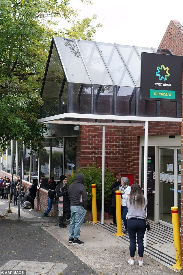 More than 3,000 millionaires claiming JobSeeker will be kicked off as asset limits are introduced on Friday. Pictured: Australians queue outside a Centrelink office at the beginning of the pandemic